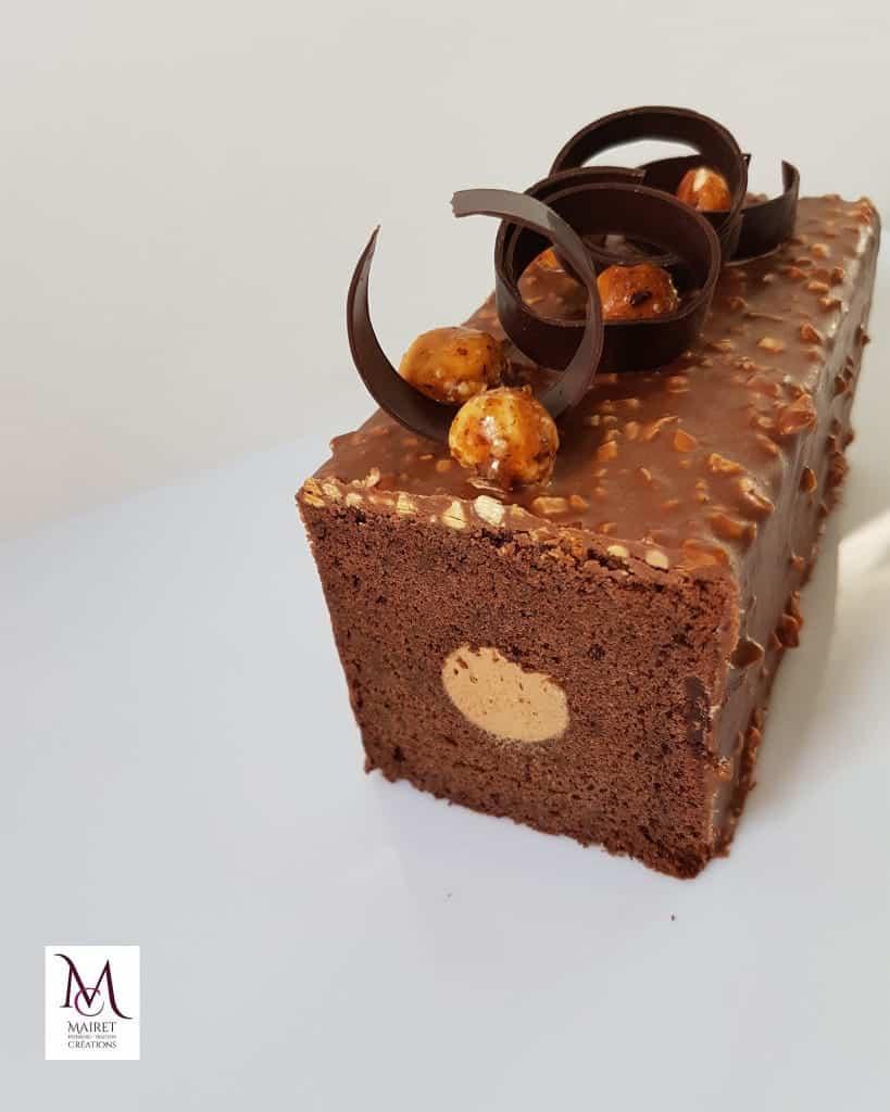 CAKE CHOCOLAT/CARAMEL BEURRE SALÉ : un cake moelleux au chocolat noir garnis,en insert,d'une ganache au caramel beurre salé, un glaçage aux amandes grillées pour plus de gourmandise.