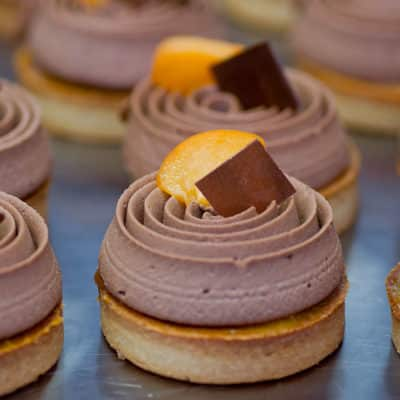 Tartelette tourbillon d'abricot : Sur une pâte sablée amande/fleur de sel, un confit d'abricot ultra frais et un cœur de caramel, aux cacahuètes! Sublimée par une chantilly de chocolat au lait.